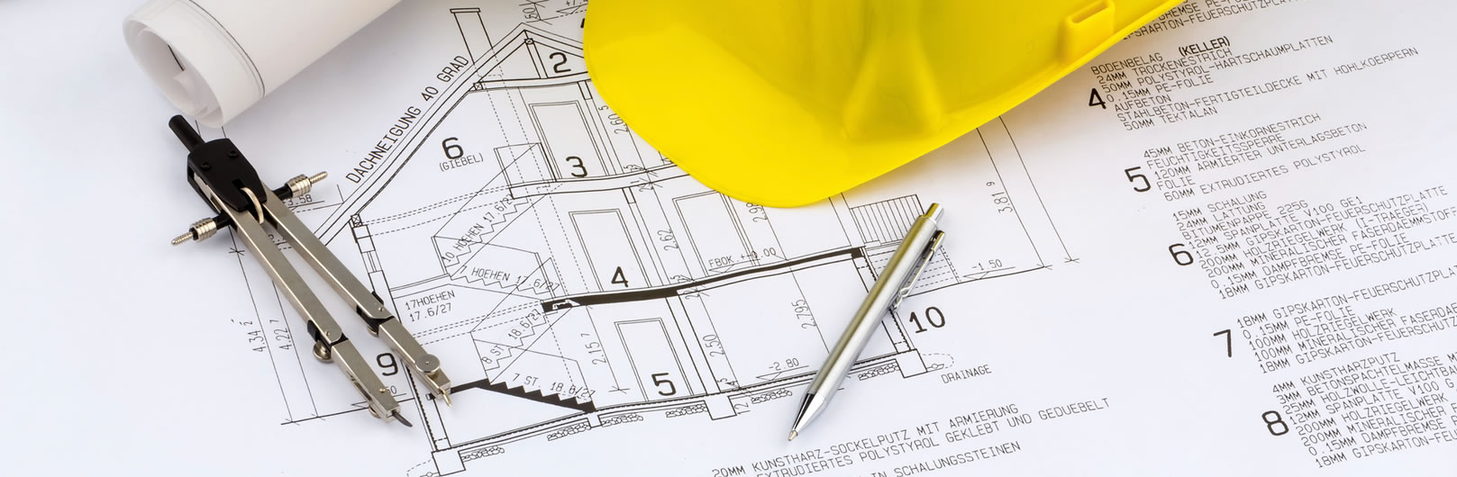 Building plans on a table with pen